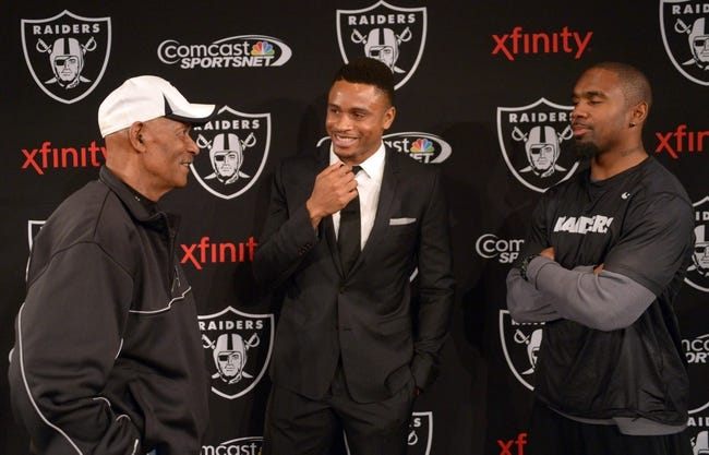Dec 27, 2013; Alameda, CA, USA; Oakland Raiders former cornerback Nnamdi Asomugha (center) talks with Willie Brown (left) and Charles Woodson at press conference to announce his retirement at Oakland Raiders Practice Facility. Mandatory Credit: Kirby Lee-USA TODAY Sports