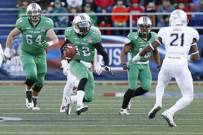 Dec 27, 2013; Annapolis, MD, USA; Marshall Thundering Herd quarterback Rakeem Cato (12) runs with the ball in front of Maryland Terrapins defensive back Sean Davis (21) in the second half during the 2013 Military Bowl at Navy Marine Corps Memorial Stadium. Mandatory Credit: Geoff Burke-USA TODAY Sports