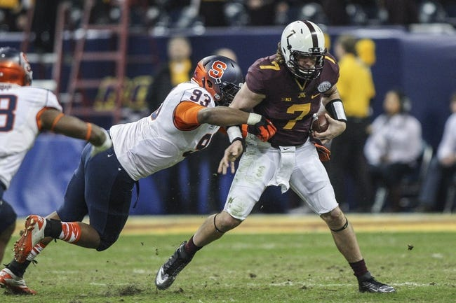 Dec 27, 2013; Houston, TX, USA; Minnesota Golden Gophers quarterback Mitch Leidner (7) runs with the ball during the second quarter of the Texas Bowl as Syracuse Orange defensive end Micah Robinson (93) makes a tackle at Reliant Stadium . Mandatory Credit: Troy Taormina-USA TODAY Sports