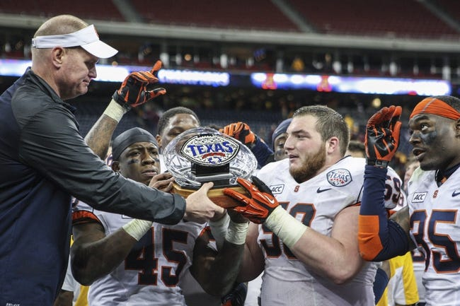 Dec 27, 2013; Houston, TX, USA; Syracuse Orange head coach Scott Shafer hands the Texas Bowl trophy to his team after defeating the Minnesota Golden Gophers 21-17 at Reliant Stadium . Mandatory Credit: Troy Taormina-USA TODAY Sports