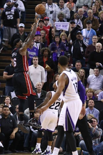 Dec 27, 2013; Sacramento, CA, USA; Miami Heat small forward LeBron James (6) scores a three point basket against the Sacramento Kings during overtime at Sleep Train Arena. The Sacramento Kings defeated the Miami Heat 108-103 in overtime. Mandatory Credit: Kelley L Cox-USA TODAY Sports