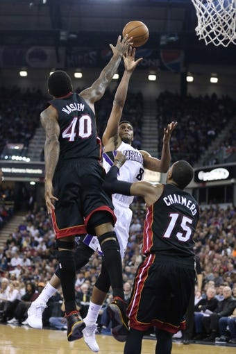 Dec 27, 2013; Sacramento, CA, USA; Sacramento Kings small forward Rudy Gay (8) goes up for a basket between Miami Heat power forward Udonis Haslem (40) and point guard Mario Chalmers (15) during the fourth quarter at Sleep Train Arena. The Sacramento Kings defeated the Miami Heat 108-103 in overtime. Mandatory Credit: Kelley L Cox-USA TODAY Sports