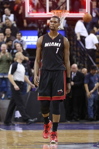 Dec 27, 2013; Sacramento, CA, USA; Miami Heat center Chris Bosh (1) returns to the bench at the end of regulation of the fourth quarter against the Sacramento Kings at Sleep Train Arena. The Sacramento Kings defeated the Miami Heat 108-103 in overtime. Mandatory Credit: Kelley L Cox-USA TODAY Sports