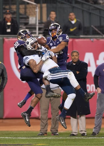 Dec 27, 2013; San Francisco, CA, USA; Washington Huskies defensive back Tre Watson (32) and defensive back Marcus Peters (21) defend a pass to Brigham Young Cougars wide receiver Cody Hoffman (2) during the fourth quarter at AT&T Park. The Washington Huskies defeated the Brigham Young Cougars 31-16. Mandatory Credit: Ed Szczepanski-USA TODAY Sports