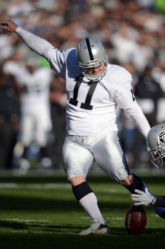 Dec 22, 2013; San Diego, CA, USA; Oakland Raiders kicker Sebastian Janikowski (11) attempts a field goal against the San Diego Chargers at Qualcomm Stadium. Mandatory Credit: Kirby Lee-USA TODAY Sports