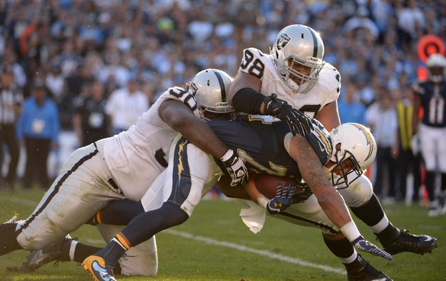 Dec 22, 2013; San Diego, CA, USA; Oakland Raiders defensive tackles Pat Sims (90) and Vance Walker (98) tackle San Diego Chargers running back Ryan Matthews  at Qualcomm Stadium. The Chargers won 26-13. Mandatory Credit: Kirby Lee-USA TODAY Sports