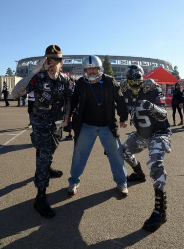 Dec 22, 2013; San Diego, CA, USA; Oakland Raiders fans Jesse Neugarton (left) aka Sarge and Geoff Skarr (center) and Ben Reneau (Raiderman) tailgate before the game against the San Diego Chargers at Qualcomm Stadium. Mandatory Credit: Kirby Lee-USA TODAY Sports