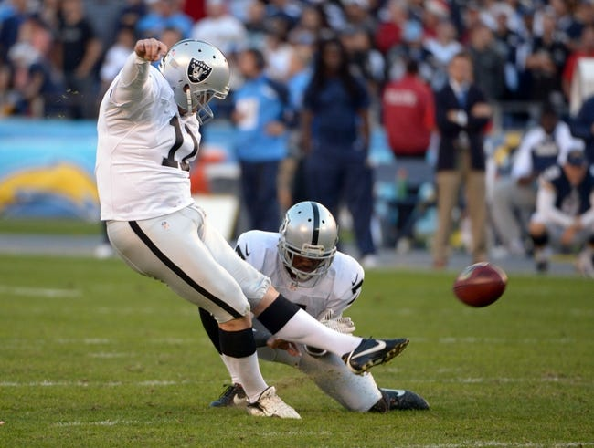 Dec 22, 2013; San Diego, CA, USA; Oakland Raiders kicker Sebastian Janikowski (11) attempts a field goal out of the hold of Marquette King (7) against the San Diego Chargers at Qualcomm Stadium. Mandatory Credit: Kirby Lee-USA TODAY Sports