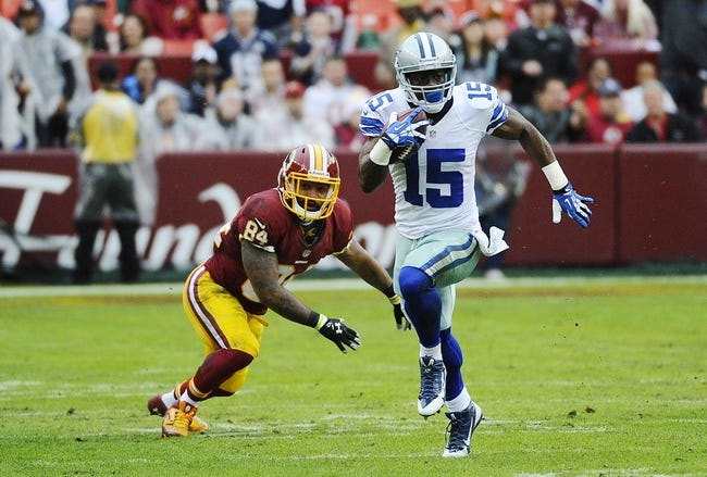 Dec 22, 2013; Landover, MD, USA; Dallas Cowboys kick returner Micheal Spurlock (15) avoids the tackle by Washington Redskins tight end Niles Paul (84) during the first half at FedEx Field. Mandatory Credit: Brad Mills-USA TODAY Sports