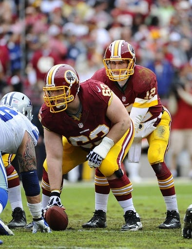 Dec 22, 2013; Landover, MD, USA; Washington Redskins quarterback Kirk Cousins (12) prepares to take the snap from Washington Redskins center Will Montgomery (63) against the Dallas Cowboys during the first half at FedEx Field. Mandatory Credit: Brad Mills-USA TODAY Sports
