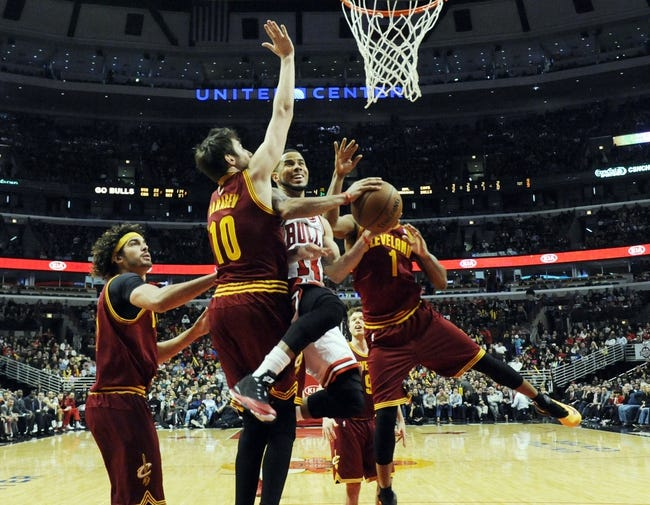 Dec 21, 2013; Chicago, IL, USA; Chicago Bulls point guard D.J. Augustin (14) is defended by Cleveland Cavaliers shooting guard Sergey Karasev (10) during the second half at the United Center. T'he Chicago Bulls defeated the Cleveland Cavaliers 100-84. Mandatory Credit: David Banks-USA TODAY Sports