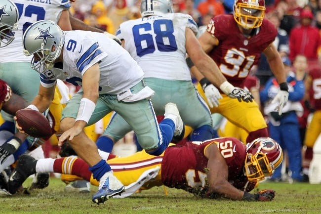 Dec 22, 2013; Landover, MD, USA; Dallas Cowboys quarterback Tony Romo (9) scrambles from Washington Redskins outside linebacker Rob Jackson (50) in the fourth quarter at FedEx Field. Romo was injured on the play and is out for the season. The Cowboys won 24-23. Mandatory Credit: Geoff Burke-USA TODAY Sports