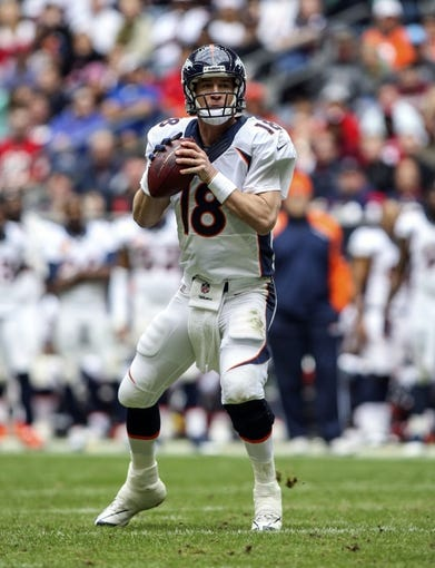 Dec 22, 2013; Houston, TX, USA; Denver Broncos quarterback Peyton Manning (18) looks for an open receiver during the second quarter against the Houston Texans at Reliant Stadium. Mandatory Credit: Troy Taormina-USA TODAY Sports