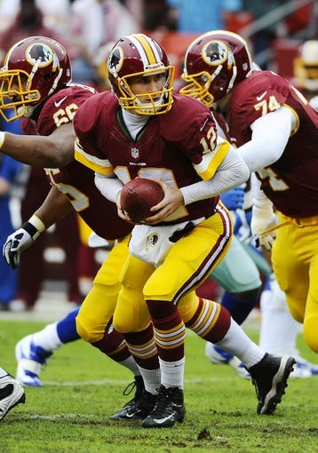 Dec 22, 2013; Landover, MD, USA; Washington Redskins quarterback Kirk Cousins (12) hands off against the Dallas Cowboys during the first half at FedEx Field. Mandatory Credit: Brad Mills-USA TODAY Sports
