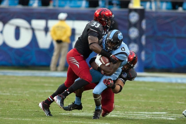 Dec 28, 2013; Charlotte, NC, USA. North Carolina Tar Heels running back T.J. Logan (8) runs the ball during the second quarter against the Cincinnati Bearcats at Bank of America Stadium. Mandatory Credit: Jeremy Brevard-USA TODAY Sports