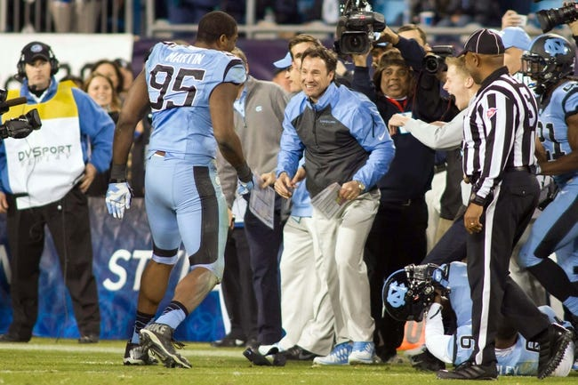 Dec 28, 2013; Charlotte, NC, USA; North Carolina Tar Heels head coach Larry Fedora smiles after defensive end Kareem Martin (95) dumped gatorade over him during the final minutes of the fourth quarter of the Belk Bowl against the Cincinnati Bearcats at Bank of America Stadium. Carolina defeated Cincinnati 39-17. Mandatory Credit: Jeremy Brevard-USA TODAY Sports