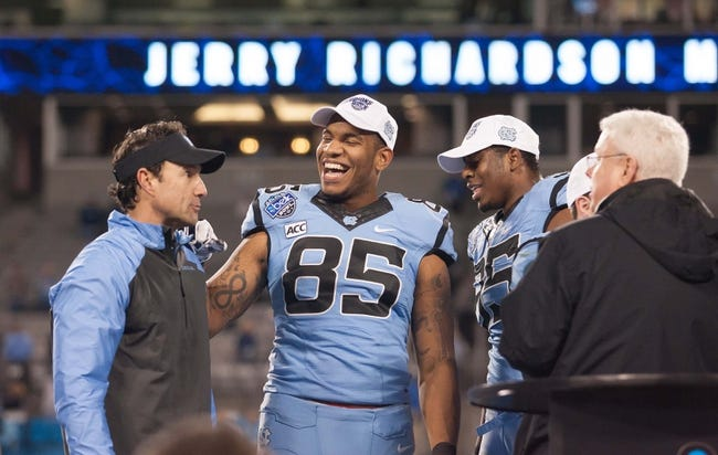 Dec 28, 2013; Charlotte, NC, USA; North Carolina Tar Heels tight end Eric Ebron (85) laughs during the award ceremony with  head coach Larry Fedora after defeating the Cincinnati Bearcats in the Belk Bowl at Bank of America Stadium. Carolina defeated Cincinnati 39-17. Mandatory Credit: Jeremy Brevard-USA TODAY Sports