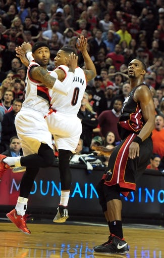 Dec 28, 2013; Portland, OR, USA; Portland Trail Blazers point guard Mo Williams (25) and point guard Damian Lillard (0) watch as Miami Heat center Chris Bosh (1) makes the game-winning shot during the fourth quarter of the game at the Moda Center. The Heat won the game 108-107. Mandatory Credit: Steve Dykes-USA TODAY Sports