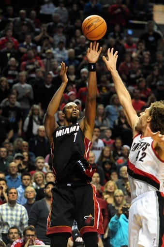 Dec 28, 2013; Portland, OR, USA; Miami Heat center Chris Bosh (1) hits a shot over Portland Trail Blazers center Robin Lopez (42) late during the fourth quarter of the game at the Moda Center. The Heat won the game 108-107. Mandatory Credit: Steve Dykes-USA TODAY Sports