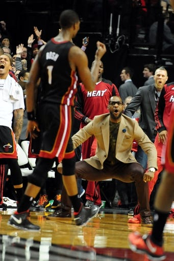 Dec 28, 2013; Portland, OR, USA; Miami Heat small forward LeBron James (middle) reacts after center Chris Bosh (1) hit the game winning shot during the fourth quarter of the game against the Portland Trail Blazers at the Moda Center. The Heat won the game 108-107. Mandatory Credit: Steve Dykes-USA TODAY Sports