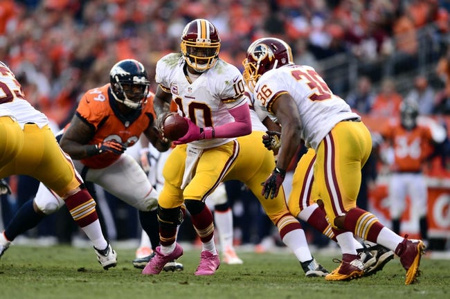 Oct 27, 2013; Denver, CO, USA; Washington Redskins quarterback Robert Griffin III (10) prepares to hand off to fullback Darrel Young (36) in the third quarter against the Denver Broncos at Sports Authority Field at Mile High. Mandatory Credit: Ron Chenoy-USA TODAY Sports