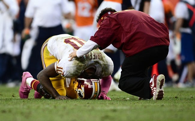 Oct 27, 2013; Denver, CO, USA; Washington Redskins quarterback Robert Griffin III (10) lays injured after being sacked in the fourth quarter against the Denver Broncos at Sports Authority Field at Mile High. Mandatory Credit: Ron Chenoy-USA TODAY Sports