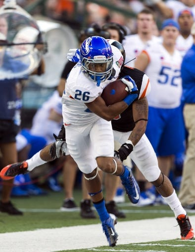 Dec 24, 2013; Honolulu, HI, USA; Boise State Broncos running back Devan Demas (26) breaks away from Oregon State Beavers safety Tyrequek Zimmerman (8) during the 2013 Hawaii Bowl at Aloha Stadium. Mandatory Credit: Marco Garcia-USA TODAY Sports