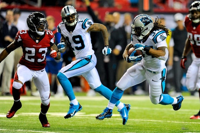 Dec 29, 2013; Atlanta, GA, USA; Carolina Panthers running back DeAngelo Williams (34) runs with the ball against Atlanta Falcons cornerback Robert Alford (23) during the second half at the Georgia Dome. The Panthers defeated the Falcons 21-20. Mandatory Credit: Dale Zanine-USA TODAY Sports