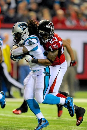 Dec 29, 2013; Atlanta, GA, USA; Carolina Panthers running back DeAngelo Williams (34) is tackled by Atlanta Falcons cornerback Robert Alford (23) during the second half at the Georgia Dome. The Panthers defeated the Falcons 21-20. Mandatory Credit: Dale Zanine-USA TODAY Sports