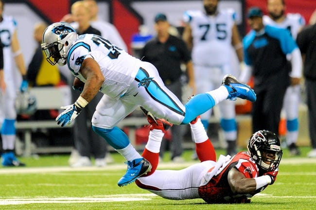 Dec 29, 2013; Atlanta, GA, USA; Carolina Panthers fullback Mike Tolbert (35) breaks a tackle by Atlanta Falcons linebacker Joplo Bartu (59) during the second half at the Georgia Dome. The Panthers defeated the Falcons 21-20. Mandatory Credit: Dale Zanine-USA TODAY Sports