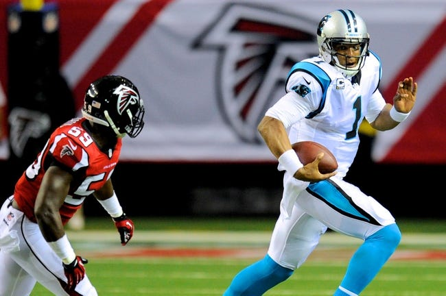 Dec 29, 2013; Atlanta, GA, USA; Carolina Panthers quarterback Cam Newton (1) runs with the ball against Atlanta Falcons linebacker Joplo Bartu (59) during the second half at the Georgia Dome. The Panthers defeated the Falcons 21-20. Mandatory Credit: Dale Zanine-USA TODAY Sports