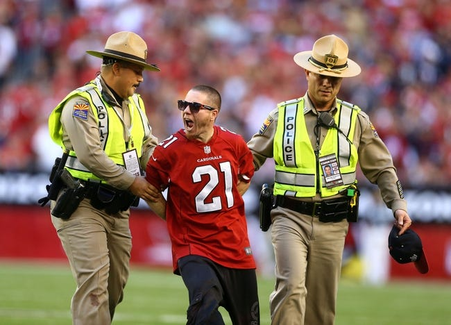 Dec 29, 2013; Phoenix, AZ, USA; An Arizona Cardinals fan reacts as he is escorted off the field by police after running onto the field in the second half against the San Francisco 49ers at University of Phoenix Stadium. The 49ers defeated the Cardinals 23-20. Mandatory Credit: Mark J. Rebilas-USA TODAY Sports