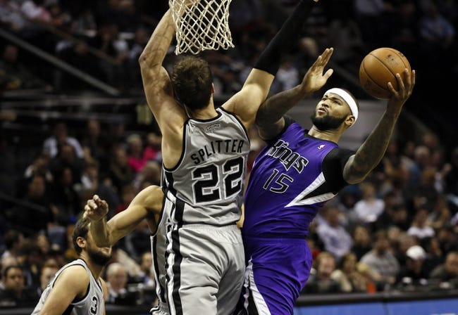Dec 29, 2013; San Antonio, TX, USA; Sacramento Kings center DeMarcus Cousins (15) drives to the basket as San Antonio Spurs forward Tiago Splitter (22) defends during the second half at the AT&T Center. The Spurs won 112-104. Mandatory Credit: Soobum Im-USA TODAY Sports