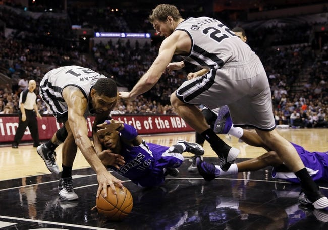 Dec 29, 2013; San Antonio, TX, USA; San Antonio Spurs forward Tim Duncan (left) and Sacramento Kings guard Ben McLemore (right) dive for the ball during the second half at the AT&T Center. The Spurs won 112-104. Mandatory Credit: Soobum Im-USA TODAY Sports