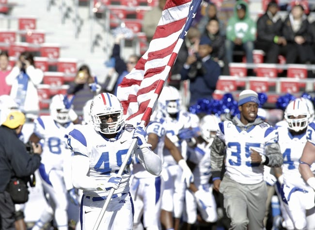Dec 30, 2013; Fort Worth, TX, USA; Middle Tennessee Blue Raiders defensive back Steve Rhodes (49) carries the American flag on to the field before the game against the Navy Midshipmen  at Amon G. Carter Stadium.  Navy beat Middle Tennessee 24-6. Mandatory Credit: Tim Heitman-USA TODAY Sports