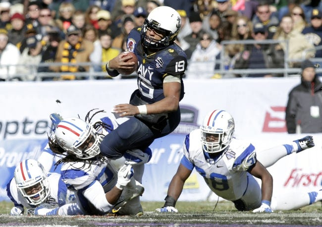 Dec 30, 2013; Fort Worth, TX, USA; Navy Midshipmen quarterback Keenan Reynolds (19) is tackled by  Middle Tennessee Blue Raiders linebacker Christian Henry (28) and linebacker T.T. Barber (38) in the third quarter of the game  at Amon G. Carter Stadium.  Navy beat Middle Tennessee 24-6. Mandatory Credit: Tim Heitman-USA TODAY Sports