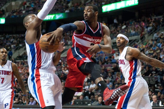 Dec 30, 2013; Auburn Hills, MI, USA; Washington Wizards point guard John Wall (2) passes around Detroit Pistons power forward Greg Monroe (10) during the third quarter at The Palace of Auburn Hills. Washington won 106-99. Mandatory Credit: Tim Fuller-USA TODAY Sports