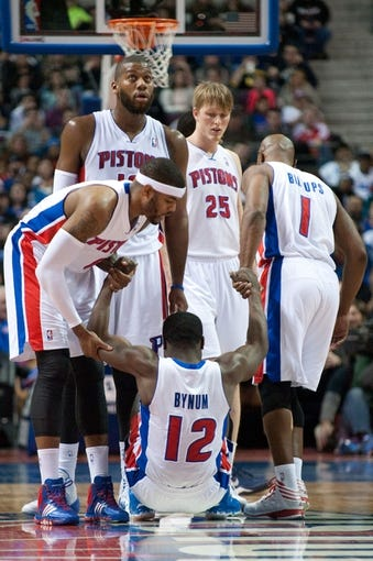 Dec 30, 2013; Auburn Hills, MI, USA; Detroit Pistons point guard Will Bynum (12) is helped up by teammates during the third quarter against the Washington Wizards at The Palace of Auburn Hills. Washington won 106-99. Mandatory Credit: Tim Fuller-USA TODAY Sports