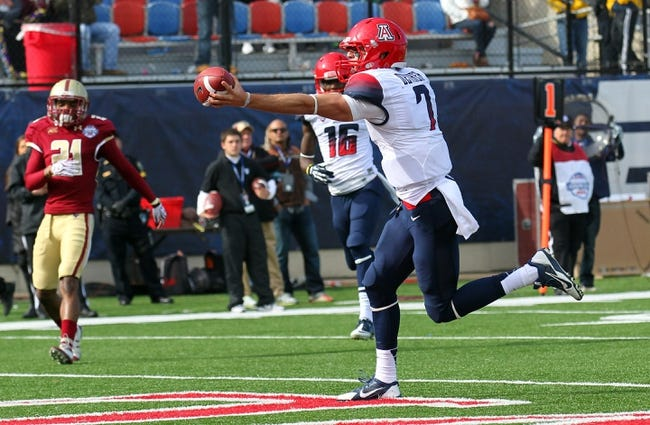 Dec 31, 2013; Shreveport, LA, USA; Arizona Wildcats quarterback B.J. Denker (7) carries the ball for a touchdown against the Boston College Eagles in the third quarter at Independence Stadium. Arizona defeated Boston College 42-19. Mandatory Credit: Crystal LoGiudice-USA TODAY Sports