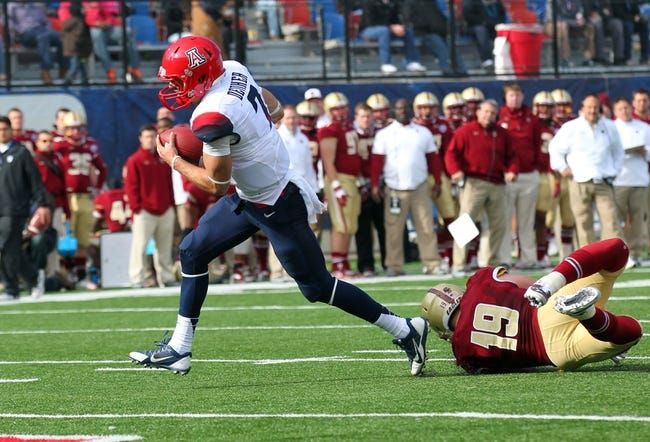 Dec 31, 2013; Shreveport, LA, USA; Arizona Wildcats quarterback B.J. Denker (7) carries the ball in front of Boston College Eagles defensive back Sean Sylvia (19) on his way to scoring a touchdown in the third quarter at Independence Stadium. Arizona defeated Boston College 42-19. Mandatory Credit: Crystal LoGiudice-USA TODAY Sports