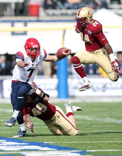Dec 31, 2013; Shreveport, LA, USA; Arizona Wildcats quarterback B.J. Denker (7) carries the ball in front of Boston College Eagles linebacker Steele Divitto (49) and linebacker Kevin Pierre-Louis (24) in the second half at Independence Stadium. Arizona defeated Boston College 42-19. Mandatory Credit: Crystal LoGiudice-USA TODAY Sports