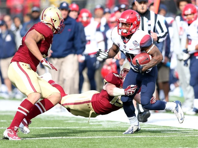 Dec 31, 2013; Shreveport, LA, USA; Arizona Wildcats wide receiver Samajie Grant (10) is tackled by Boston College Eagles defensive back Sean Sylvia (behind) as he carries the ball in the second half at Independence Stadium. Arizona defeated Boston College 42-19. Mandatory Credit: Crystal LoGiudice-USA TODAY Sports