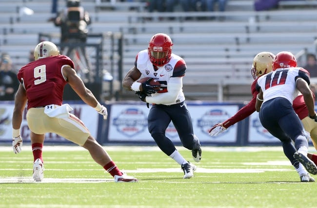 Dec 31, 2013; Shreveport, LA, USA; Arizona Wildcats running back Ka'Deem Carey (25) carries the ball beside Boston College Eagles defensive back Dominique Williams (9) in the first half at Independence Stadium. Arizona defeated Boston College 42-19. Mandatory Credit: Crystal LoGiudice-USA TODAY Sports