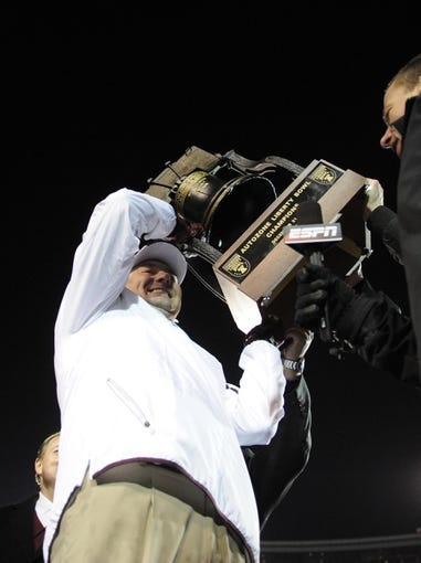 Dec 31, 2013; Memphis, TN, USA; Mississippi State Bulldogs head coach Dan Mullen holds up trophy after beating Rice Owls  at Liberty Bowl Memorial Stadium. Mississippi State Bulldogs beat Rice Owls 44 - 7. Mandatory Credit: Justin Ford-USA TODAY Sports