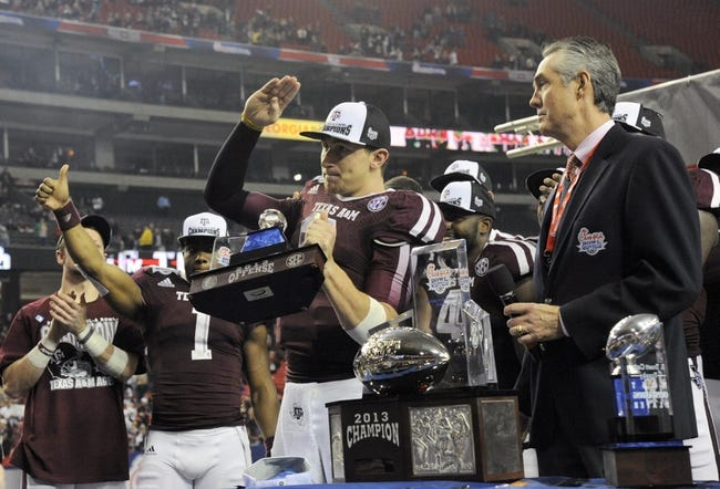 Dec 31, 2013; Atlanta, GA, USA;  Texas A&M Aggies quarterback Johnny Manziel (2) salutes the fans alongside Chick-fil-a executive vice president Steve Robinson (right) after their victory over the Duke Blue Devils 52-48 and winning the offensive player of the game in the 2013 Chick-fil-a Bowl at the Georgia Dome. Mandatory Credit: Dale Zanine-USA TODAY Sports