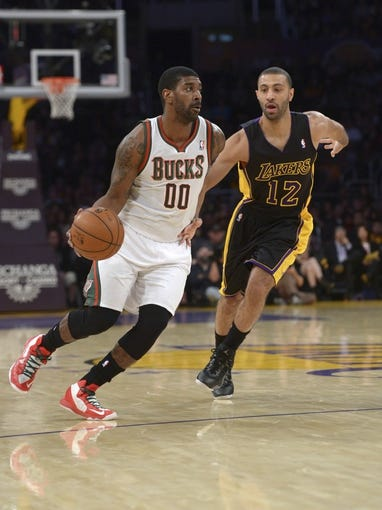 Dec 31, 2013; Los Angeles, CA, USA; Milwaukee Bucks guard O.J. Mayo (00) is defended by Los Angeles Lakers guard Kendall Marshall (12) during the game at Staples Center. Mandatory Credit: Kirby Lee-USA TODAY Sports