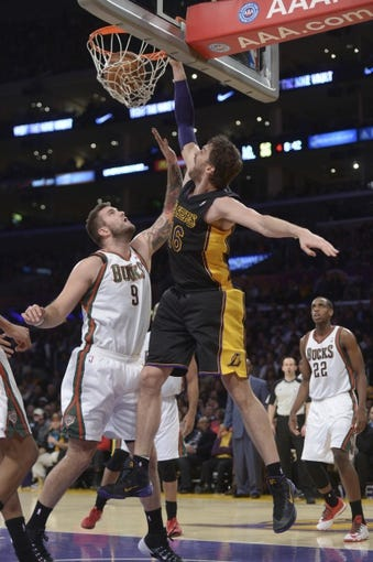 Dec 31, 2013; Los Angeles, CA, USA; Los Angeles Lakers forward Pau Gasol (16) dunks the ball against Milwaukee Bucks center Miroslav Radjuljica (9) during the game at Staples Center. The Bucks defeated the Lakers 94-79. Mandatory Credit: Kirby Lee-USA TODAY Sports