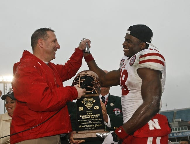 Jan 1, 2014; Jacksonville, FL, USA; Nebraska Cornhuskers head coach Bo Pelini reacts as he hands the Gator Bowl most valuable player trophy to wide receiver Quincy Enunwa (18) after their game against the Georgia Bulldogs at EverBank Field. The Nebraska Cornhuskers beat the Georgia Bulldogs 24-19. Mandatory Credit: Phil Sears-USA TODAY Sports