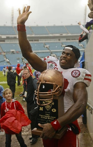 Jan 1, 2014; Jacksonville, FL, USA; Nebraska Cornhuskers wide receiver Quincy Enunwa (18) waves to fans  with his MVP trophy after their game against the Georgia Bulldogs at EverBank Field. The Nebraska Cornhuskers beat the Georgia Bulldogs 24-19. Mandatory Credit: Phil Sears-USA TODAY Sports