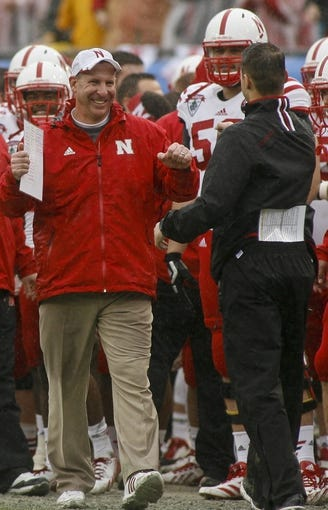 Jan 1, 2014; Jacksonville, FL, USA; Nebraska Cornhuskers head coach Bo Pelini celebrates with his staff in the final seconds of the fourth quarter of their game against the Georgia Bulldogs at EverBank Field. The Nebraska Cornhuskers beat the Georgia Bulldogs 24-19. Mandatory Credit: Phil Sears-USA TODAY Sports